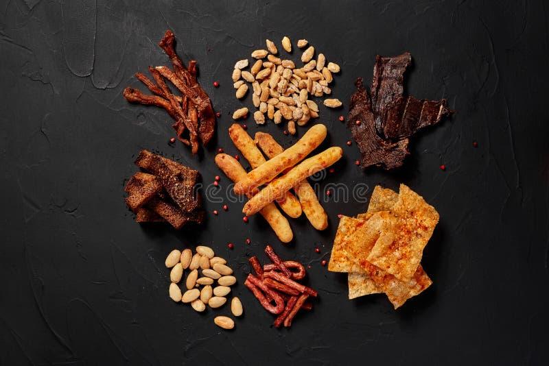 A vista superior de vários petiscos da cerveja gosta do amendoim, biscoitos, salsichas, microplaquetas, espasmódicas, varas do qu fotografia de stock royalty free