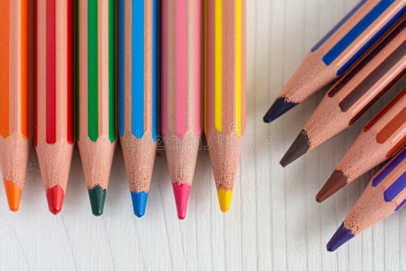Vista superior de varios lápices coloreados dispuestos verticalmente y diagonalmente en el fondo de madera blanco foto de archivo