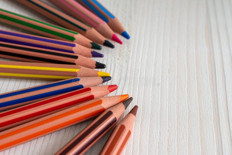 Vista superior de varios lápices coloreados para la escuela, en semicírculo, en el fondo de madera blanco fotografía de archivo libre de regalías