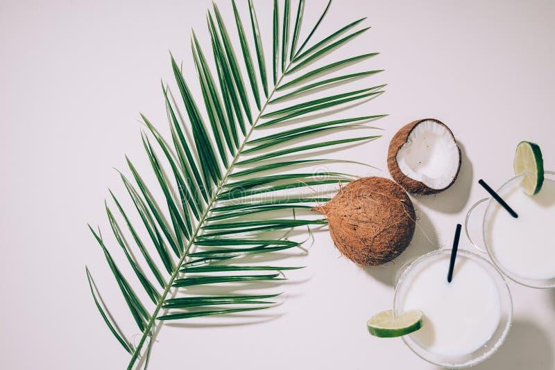 vista superior de vidrios con los cócteles del coco, cal y pajas de beber, hojas de palma verdes y cocos exóticos fotografía de archivo libre de regalías