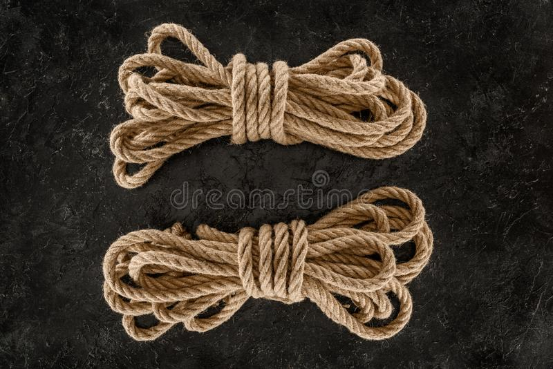 vista superior del arreglo de cuerdas marinas marrones atadas en oscuridad fotografía de archivo
