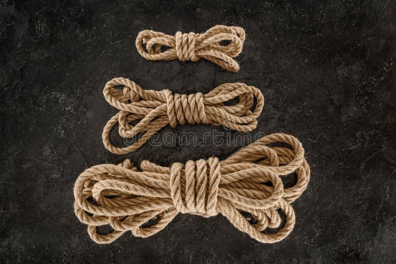 vista superior del arreglo de cuerdas marinas marrones atadas en oscuridad foto de archivo libre de regalías