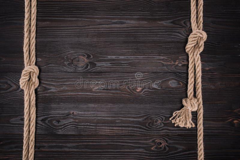 vista superior del arreglo de cuerdas náuticas marrones con los nudos en oscuridad foto de archivo