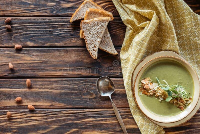 vista superior del arreglo de la sopa poner crema vegetariana con los brotes, los pedazos de pan y las almendras foto de archivo