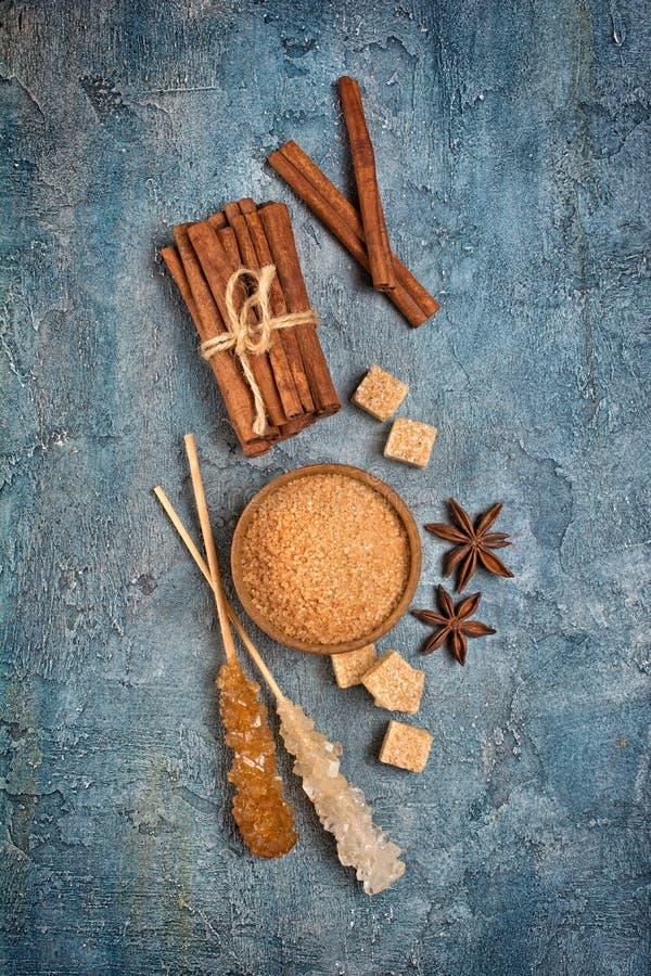 Vista superior del azúcar de caña marrón y del palillo cristalino con las especias como estrellas del canela y del anís fotografía de archivo libre de regalías