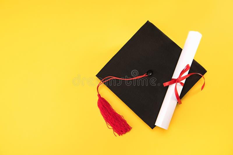 Vista superior del birrete y del diploma de la graduación en fondo amarillo foto de archivo