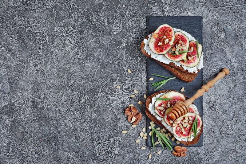 Vista superior del bocadillo vegetariano con los higos, el queso suave, la miel, la nuez y el romero en tablero negro de la pizar fotos de archivo