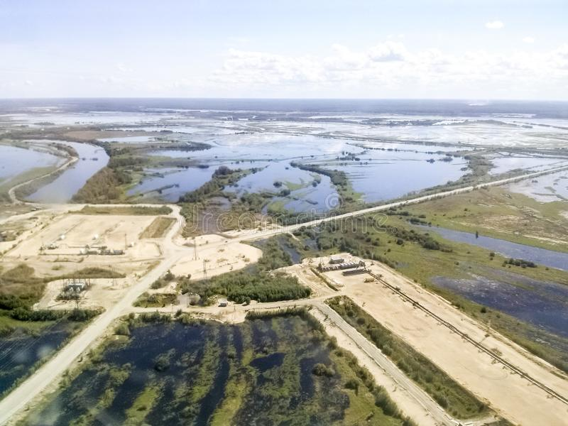 Vista superior del campo del petróleo y gas Humedales y entradas a las instalaciones industriales imagenes de archivo