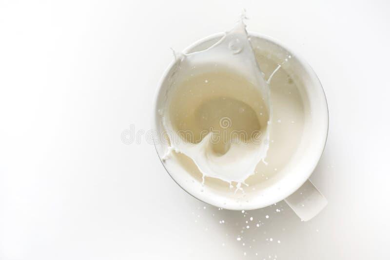 Vista superior del chapoteo de la leche fuera del vidrio imagenes de archivo