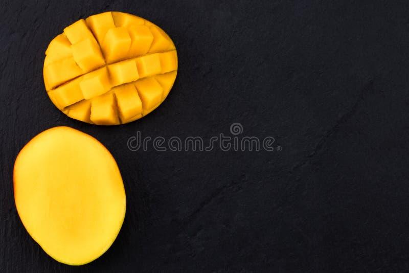 Vista superior del corte maduro del mango por la mitad y cortado en cuadritos en pizarra oscura fotos de archivo