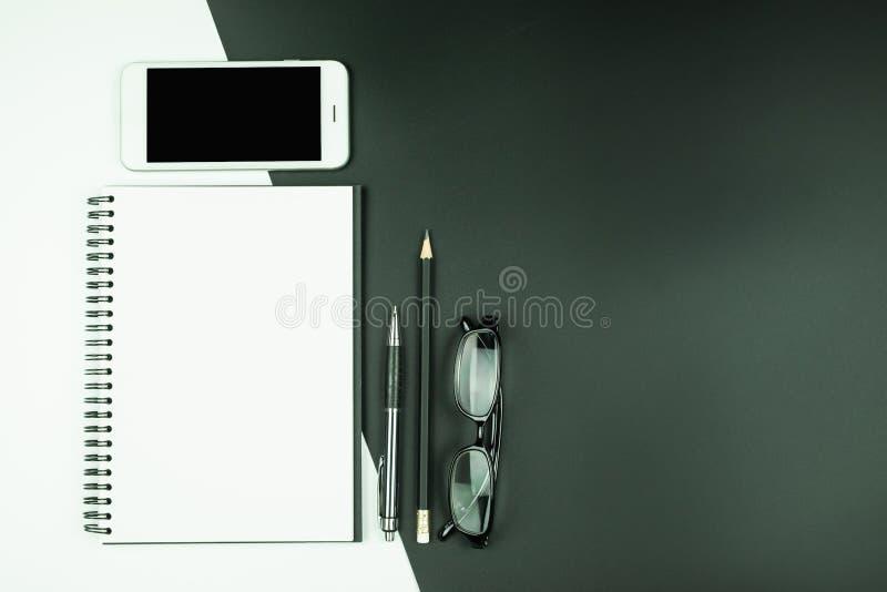 Vista superior del cuaderno abierto con el teléfono y efectos de escritorio elegantes en fondo blanco y negro imagen de archivo