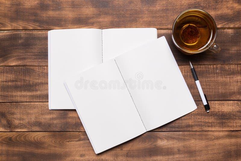 vista superior del cuaderno abierto con las páginas en blanco al lado de la taza de café en la tabla de madera aliste para añadir fotos de archivo libres de regalías