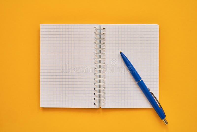 Vista superior del cuaderno abierto con las páginas en blanco y la pluma azul, cuaderno en un fondo amarillo, libreta espiral de  foto de archivo libre de regalías