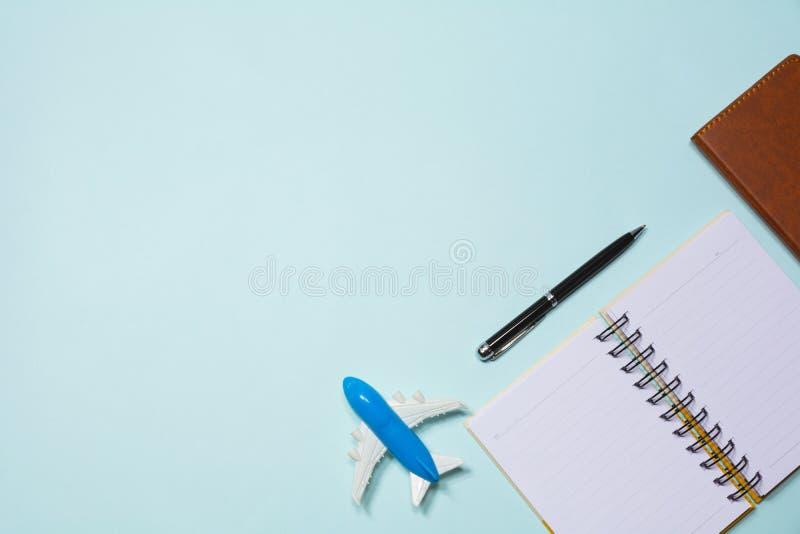 Vista superior del cuaderno con el juguete del aeroplano y de la pluma en la parte posterior del azul de cielo imagenes de archivo