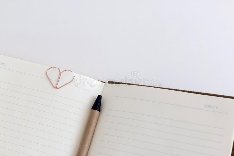 Vista superior del cuaderno o del diario en blanco abierto con el shap de la pluma y del corazón fotos de archivo