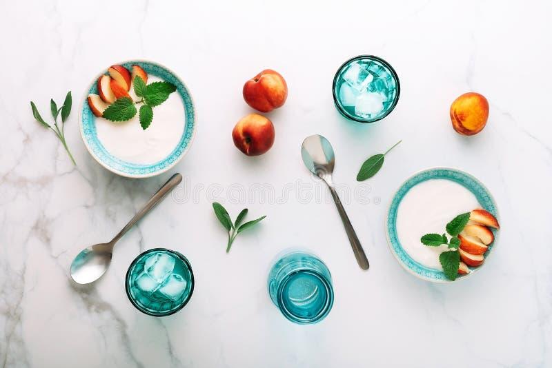 Vista superior del desayuno sano del yogur, de la fruta y del agua griegos naturales en la tabla de mármol Endecha plana imagen de archivo libre de regalías
