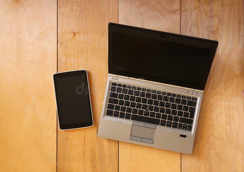 Vista superior del dispositivo y del ordenador portátil de la tableta con la pantalla en blanco lista para la mofa para arriba Im imágenes de archivo libres de regalías