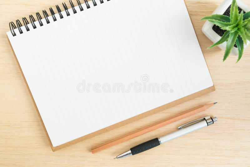 Vista superior del escritorio de oficina con el cuaderno espiral abierto en la tabla de madera imagen de archivo