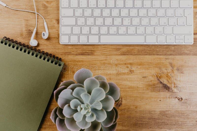 Vista superior del escritorio de oficina de madera de moda con el teclado, los auriculares blancos y los materiales de oficina imagen de archivo