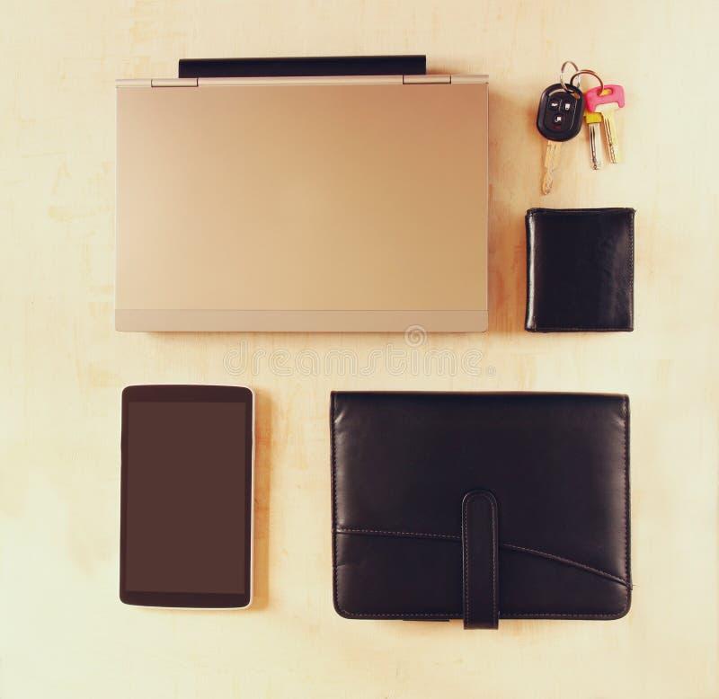 Vista superior del esencial para la persona joven o el hombre de negocios moderna Diversos objetos en fondo de madera imagen de archivo libre de regalías