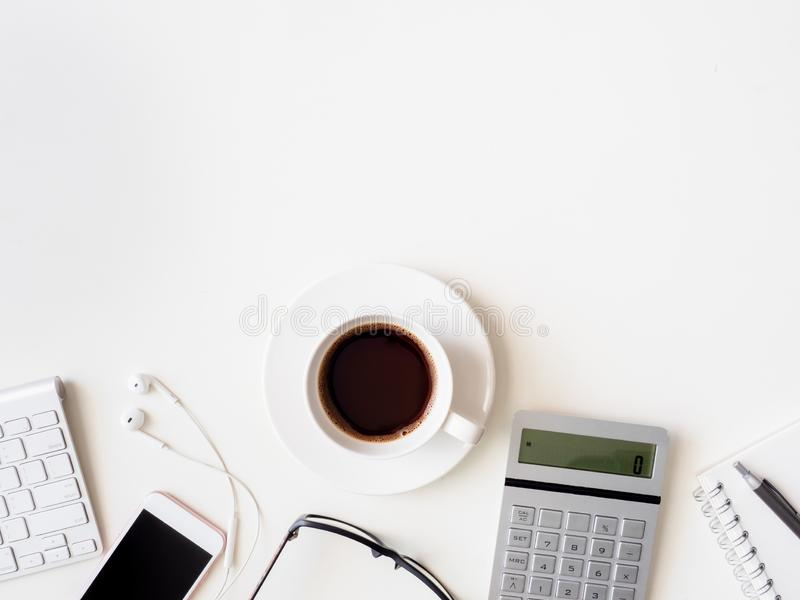 Vista superior del espacio de trabajo del escritorio de oficina con el cuaderno, el smartphone y el artilugio en el fondo blanco, imagen de archivo