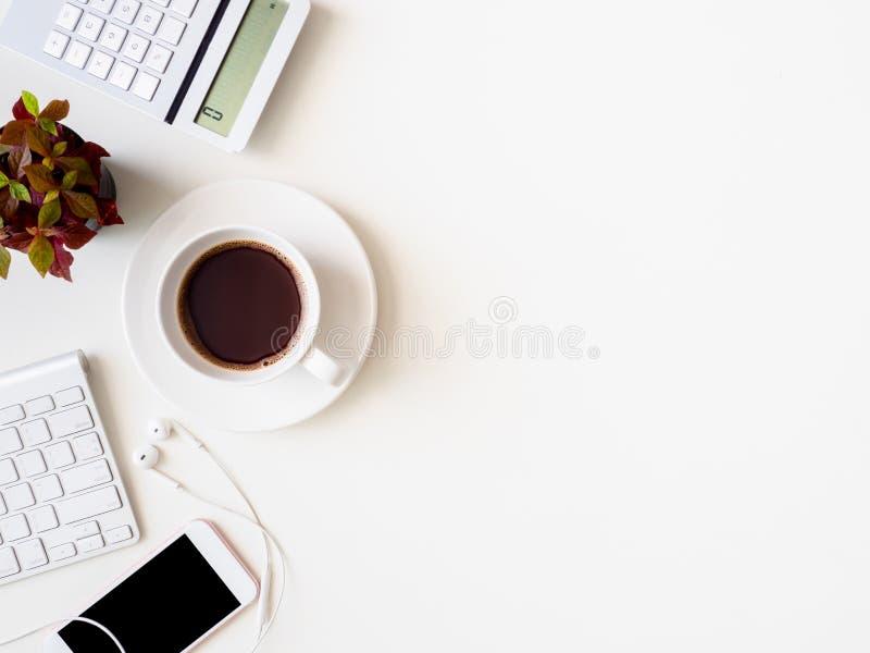 Vista superior del espacio de trabajo del escritorio de oficina con el cuaderno, el smartphone y el artilugio en el fondo blanco, foto de archivo