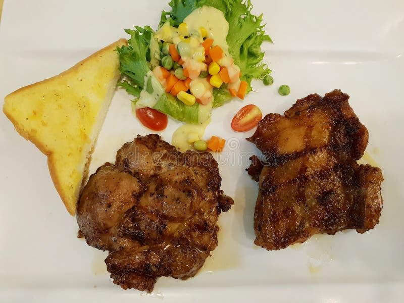 Vista superior del filete asado a la parrilla del pollo y del cerdo con la verdura de la tostada y de ensalada del ajo fotos de archivo