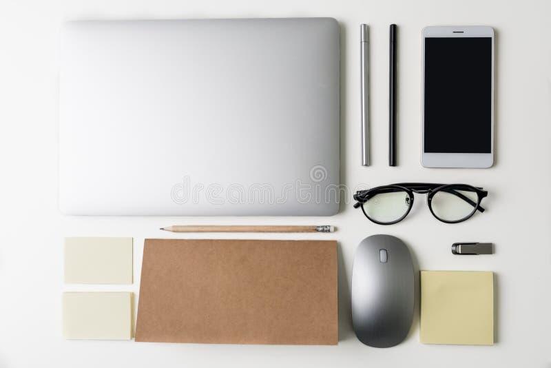 Vista superior del lugar de trabajo de la oficina Opinión plana de la endecha sobre la tabla blanca con el ordenador portátil, te foto de archivo libre de regalías