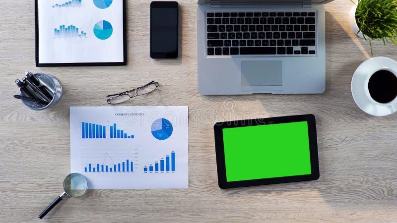 Vista superior del lugar de trabajo de la oficina, tableta con la pantalla verde que miente en la tabla, app foto de archivo