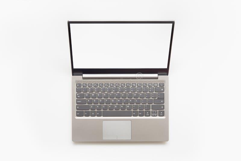 Vista superior del ordenador portátil moderno Open con el teclado inglés y la pantalla en blanco del espacio de la copia, aislada foto de archivo