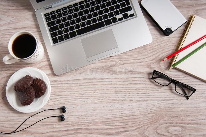 Vista superior del ordenador portátil y de la libreta con los vidrios y los auriculares en la mesa y la taza de café de madera rú foto de archivo libre de regalías