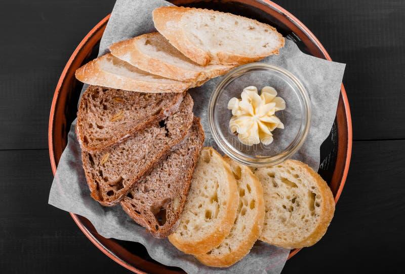Vista superior del pan integral cortado de las espiguillas del pan, del ciabatta y del centeno con mantequilla en fondo de madera fotografía de archivo