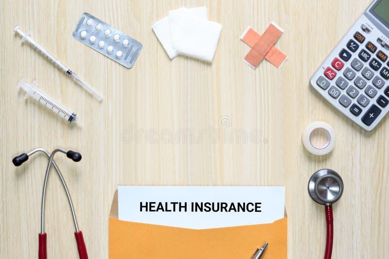 Vista superior del seguro médico en sobre de la letra con el estetoscopio fotos de archivo