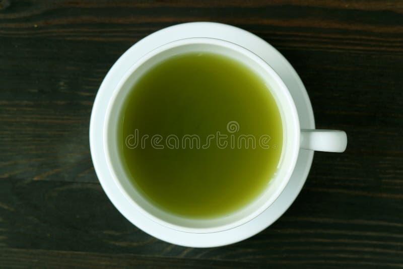 Vista superior del té verde caliente vibrante de Matcha del color verde en la tabla de madera oscura de Brown imagenes de archivo