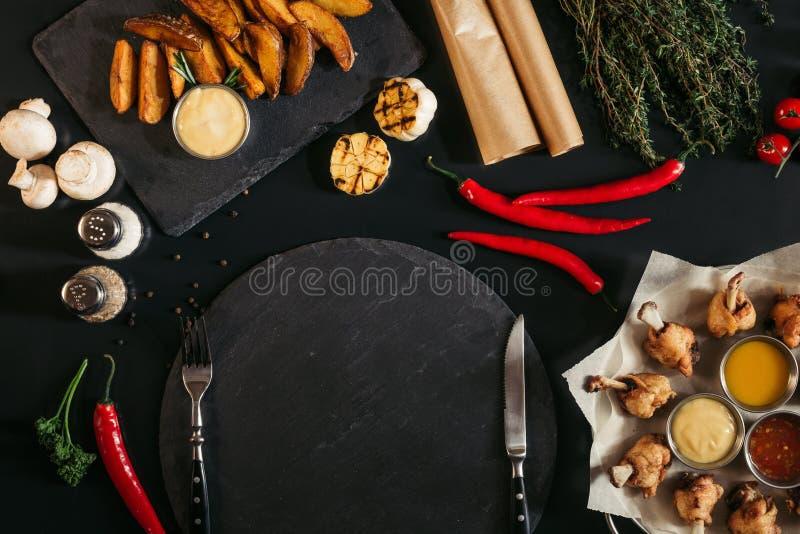 vista superior del tablero vacío de la pizarra con la bifurcación y cuchillo, patatas asadas y verduras imágenes de archivo libres de regalías