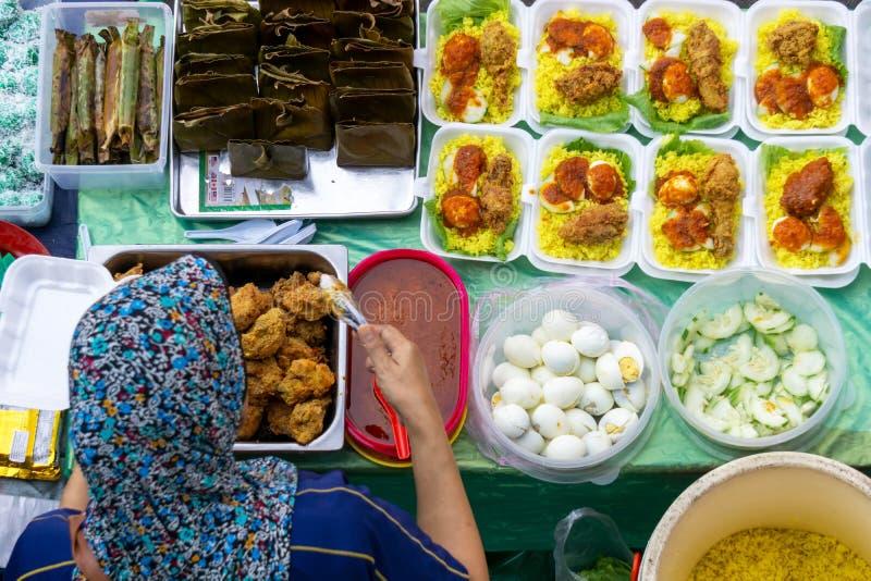 Vista superior del vendedor preparando el paquete de arroz amarillo en el puesto de comida en el mercado de comida de la ciudad de fotografía de archivo libre de regalías