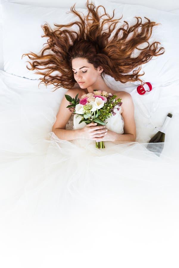 Vista superior del vestido blanco que lleva de la novia del pelirrojo que duerme en cama con las flores fotos de archivo libres de regalías