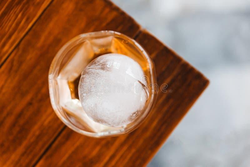 Vista superior del whisky escocés de la sola malta en vidrio de consumición con la esfera del hielo en la tabla de madera foto de archivo libre de regalías
