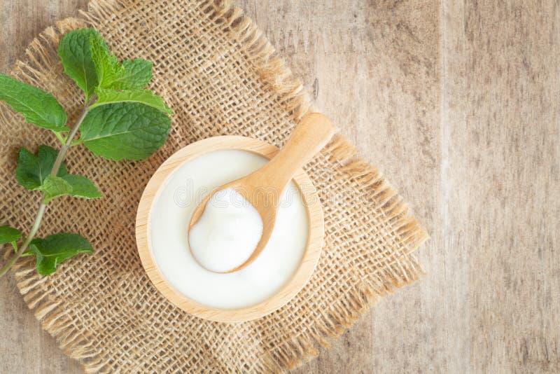 Vista superior del yogur griego natural en viejo fondo de madera de la tabla de la taza El yogur es sabroso y sano deliciosos fotografía de archivo libre de regalías