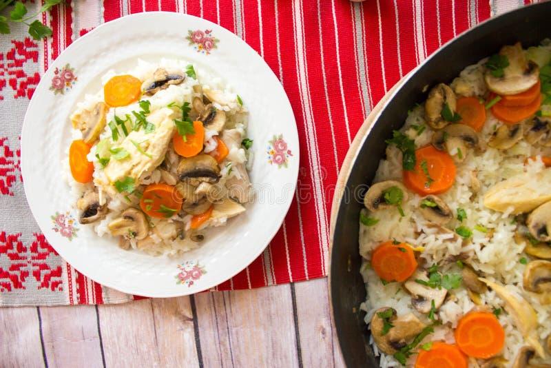Vista superior do arroz com galinha e vegetais na placa e no frigideira foto de stock