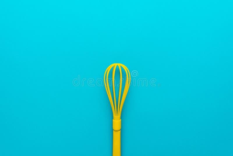 Vista superior do batedor de ovos plástico amarelo sobre o fundo do azul de turquesa com espaço da cópia fotografia de stock royalty free