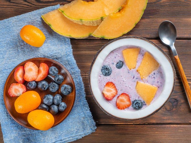 Vista superior do batido do mirtilo em uma bacia do coco com morangos e melão e kumquat em uma toalha azul com uma colher de chá fotografia de stock royalty free