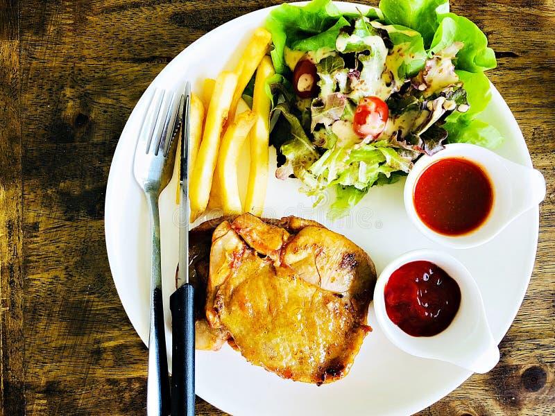 Vista superior do bife grelhado da galinha com salada e batatas fritas na tabela de madeira foto de stock