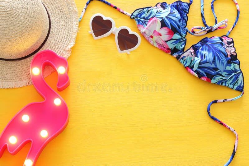 Vista superior do biquini e do chapéu fêmeas do roupa de banho da forma sobre o fundo de madeira amarelo Conceito das férias da p imagem de stock