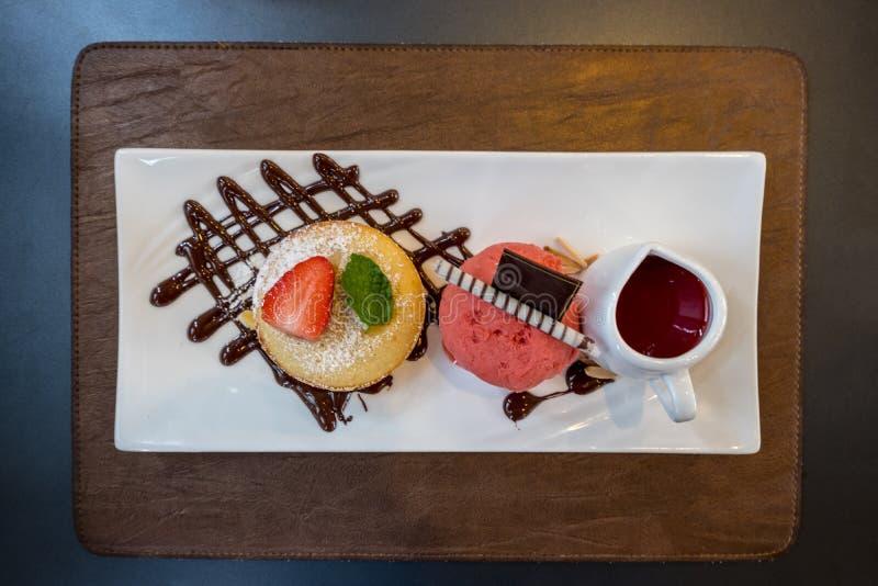 A vista superior do bolo branco da lava do chocolate serviu com gelado e molho da morango fotos de stock royalty free