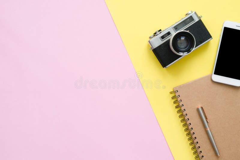Vista superior do caderno, do lápis, da tabuleta e da câmera marrons na tela cor-de-rosa e amarela da cor pastel com um espaço da fotos de stock