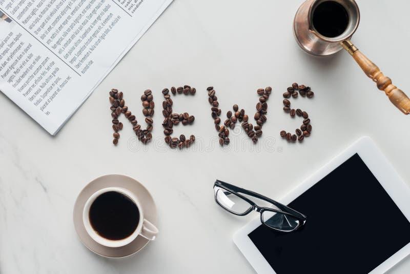 vista superior do café com a rotulação da notícia feita de feijões e de jornal de café com tabuleta imagens de stock