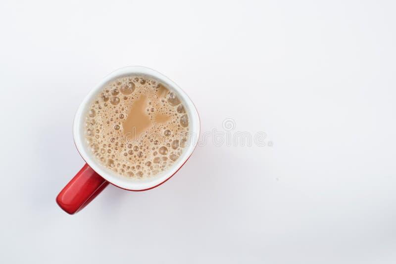 Vista superior do café do leite ou do chá espumoso do leite em uma caneca vermelha imagens de stock