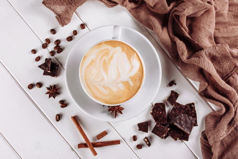 Vista superior do café ou do cappuccino quente do Latte no copo branco com espuma da arte e em feijões de café roasted na tabela  fotografia de stock royalty free
