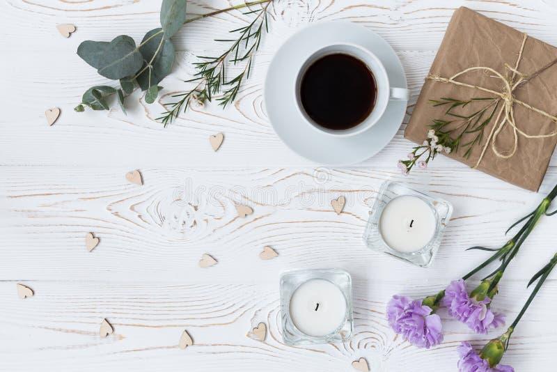 Vista superior do café, presentes envolvidos no papel de embalagem, corações, velas, flores na tabela de madeira branca Fundo com fotos de stock